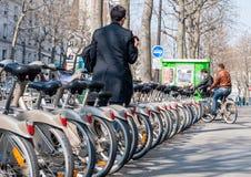 Paris Frankrike - April 02, 2009: Ung man som sätter in hans cykel på Royaltyfri Foto