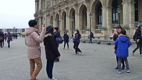 PARIS FRANKRIKE - DECEMBER, 31, 2016 Asiatiska turister som poserar och gör foto nära Louvre, berömt franskt museum Arkivbild
