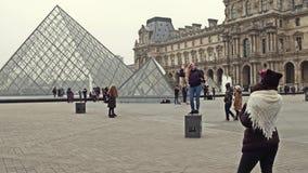 PARIS FRANKRIKE - DECEMBER, 31, 2016 Kvinnliga turister som poserar och gör foto nära Louvre, berömt franskt museum Arkivfoto