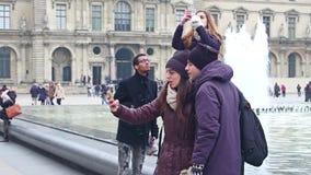PARIS FRANKRIKE - DECEMBER, 31, 2016 Multietniska par som gör selfies nära den glass pyramiden och springbrunnarna för Louvre Arkivfoto