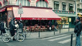 PARIS FRANKRIKE - DECEMBER, 31, 2016 Parisiskt kafé med markisen och stads- trafik på väggenomskärningen Arkivfoto