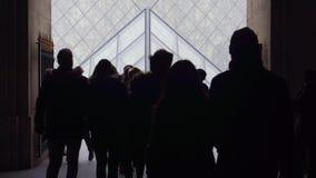 PARIS FRANKRIKE - DECEMBER, 31, 2016 Turistkonturer som går nära Louvreexponeringsglaspyramiden Populärt franskt museum Royaltyfri Foto