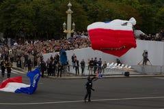 Paris Frankrike - Juli 14, 2012 Landning av fallskärmsjägare på fyrkanten under militären ståtar i Paris Arkivbilder