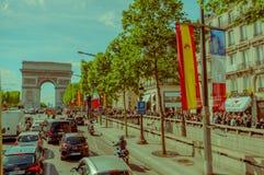 Paris Frankrike - Juni 1, 2015: I trafik som kör in mot storartad monumentbåge av triumfen Royaltyfri Foto