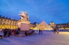 Paris Frankrike - Maj 14, 2015: Turister som besöker Louvremuseet på skymning Fotografering för Bildbyråer