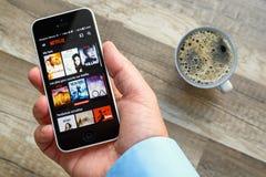 Paris Frankrike - mars 10, 2017: Mannen rymmer en smart telefon som visar filmer från Netflix Frankrike Netflix är ett underhålln Arkivfoton