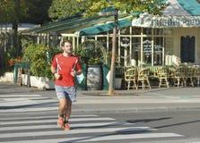 PARIS FRANKRIKE - OKTOBER 16, 2016: Den amatörmässiga löparen kör nära ett kafé på gatan av Paris Royaltyfria Bilder