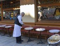 PARIS FRANKRIKE - OKTOBER 16, 2016: En äldre uppassare i traditionell form gör ren tabellen i traditionellt parisiskt kafé nära b Royaltyfria Bilder