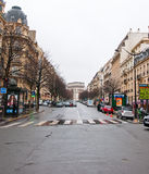 PARIS-JANUARY 10: Parisian street in a bad weather and the Arc de Triomphe in the background on January 10,2013. The Arc de Triomphe stands at the western end Stock Photos