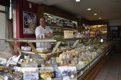 Paris Juli 17: Säljaremannen i en ost shoppar från Montmartre i Paris Fotografering för Bildbyråer
