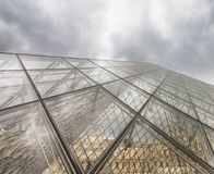 PARIS - JULY 2014: Louvre exterior architecture. Paris attracts. 40 million visitors annually Stock Image