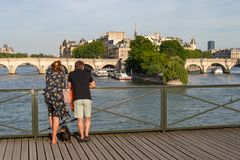 Tourists enjoying the view from Pont des Arts bridge. royalty free stock photos