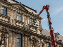 Paris maintenance workers hoisted by crane to top floor of Louvre. Paris, France, August 30, 2015: Maintenance workers hoisted by crane to top floor of Louvre Royalty Free Stock Photos