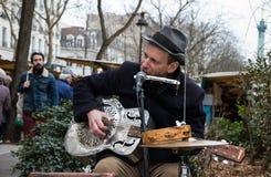 Street guitarist in Paris. PARIS - MARCH 10: Blues-rock guitarist Rene Miller playing his Dobro guitar at street market on March 10, 2013 in Paris, France Stock Images