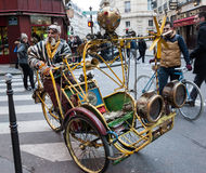 Extravagant senior rickshaw drives his unique antique vehicle in Paris. Stock Photography