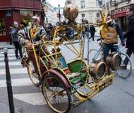 Extravagant senior rickshaw drives his unique antique vehicle in Paris. stock photography