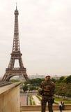 PARIS-MAY 24日2015年:在站立在宫殿Trocadero的制服的法国士兵后看艾菲尔铁塔在被覆盖的天 图库摄影