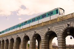 Paris Metro on the bridge. The Paris Metro is crossing the Seine River on a stone bridge stock photos