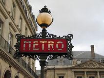 Paris Metro sign on a gray day. Paris Metro sign and streetlight on a gray day royalty free stock photos