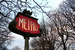 Paris Metro sign. Paris metro red sign with winter trees background royalty free stock image