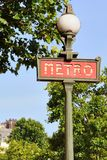 Paris Metro sign. A typical Paris metro sign with some of the classic Parisian jagged rooftops in the background Stock Image