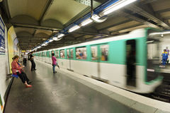 Paris Metro Train approaching staion at speed. Paris Metro train Approaching a station at speed with passengers waiting to get on royalty free stock images