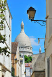 Paris,  Montmartre. Paris. View of the dome of the basilica Sacre Coeur from the narrow street of  Montmartre Royalty Free Stock Photography