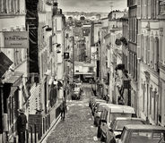 Paris, Montmartre Street. Looking down a street of hotels and restaurants (including a creperie), with shuttered buildings and people walking, on the hill in Stock Images