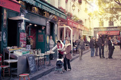 Paris montmartre street scene. Street in montmartre paris with cafe and parisians, tourists enjoying the sunny day Royalty Free Stock Photography