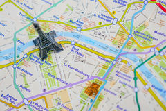 Paris name at a map with red Eiffel tower miniature. Travel Destination Paris Stock Image
