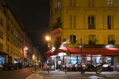 Paris by night. The people sit and talk in a cafe. Royalty Free Stock Image