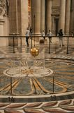View of the famous Foucault Pendulum copper ball swinging inside the Pantheon in Paris. Stock Photo