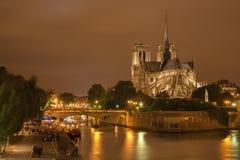 Paris - Notre-Dame domkyrka på natten och lotten av ungdomarpå flodstranden Royaltyfri Fotografi