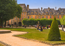 Paris, Place des Voges. People enjoying an afternoon in the Place des Voges, a popular destination for residents and tourists in Paris, France.  Located in  the Royalty Free Stock Photography