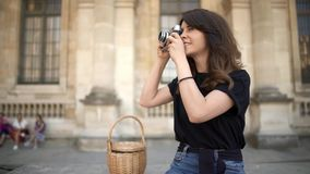 PARIS, Pretty woman making photo with a film camera on background. Old buildings in Paris on background. PARIS Pan shot left to right of young caucasian brunette stock video