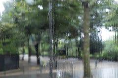 Paris in the Rain Through the Bus Window. Rain runs down the bus window adding texture to the scene outdoors - an arcade of green trees in a deserted Paris park stock photos