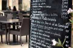 Paris France, French restaurant menu board, people eating in distance Royalty Free Stock Photos