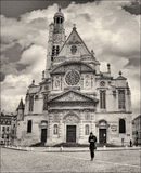 Paris: Saint-Étienne-du-Mont. The greatest beauty grows banal when seen daily. The man texts on his phone, while behind him rises one of the architectural Royalty Free Stock Photo