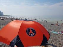 Paris Saint-Germain  sun umbrella on beach in Le Tréport, France. Rocky beach in Le Tréport, France, with an sun umbrella and the logo of Paris Saint Royalty Free Stock Images