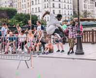 Paris skater leaps plastic barricade as people look on stock image