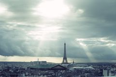Paris skyline with rooftops and the Eiffel tower on a cloudy day with sun rays. Paris symbol and iconic landmark. Famous Royalty Free Stock Images