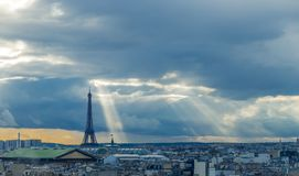 Paris skyline with rooftops and the Eiffel tower on a cloudy day with sun rays. Paris symbol and iconic landmark. Famous Royalty Free Stock Image