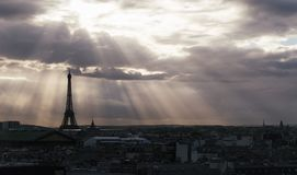 Paris skyline with rooftops and the Eiffel tower on a cloudy day with sun rays. Paris symbol and iconic landmark. Famous Royalty Free Stock Photos