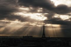 Paris skyline with rooftops and the Eiffel tower on a cloudy day with sun rays. Paris symbol and iconic landmark. Famous Stock Image