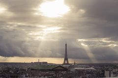 Paris skyline with rooftops and the Eiffel tower on a cloudy day with sun rays. Paris symbol and iconic landmark. Famous Royalty Free Stock Photo