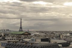 Paris skyline with rooftops and the Eiffel tower on a cloudy day. Paris symbol and iconic landmark. Famous touristic. Places and romantic travel destinations in Stock Photos