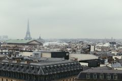 Paris skyline with rooftops and the Eiffel tower on a foggy day. Paris symbol and iconic landmark. Famous touristic. Places and romantic travel destinations in Stock Photography