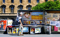 Paris. Stalls 0n the River Seine. A man stops to look at the prints and art in a stall typical of the stalls, or kiosks, along the River Seine in Paris, France Royalty Free Stock Photo