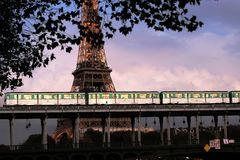 Paris subway train passing on the Bir-Hakeim bridge. Across the Seine River in front of the Eiffel Tower at sunset in Paris, France. transit métro de Paris stock images