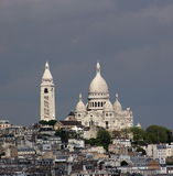 Paris_sunlit Sacre Coeur. The Cathedral of Sacre Coeur on the Mont Martre is lit by the sun and glows brightly against the dark sky. The picture was taken from Stock Photography